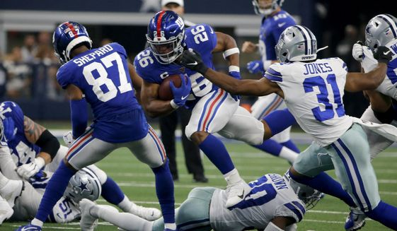 New York Giants' Sterling Shepard (87) helps clear running room for running back Saquon Barkley (26) as Dallas Cowboys cornerback Byron Jones (31) defends in the second half of a NFL football game in Arlington, Texas, Sunday, Sept. 8, 2019. (AP Photo/Michael Ainsworth)