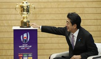 Japan's Prime Minister Shinzo Abe points to the Webb Ellis trophy during a courtesy call by World Rugby officials as part of the trophy tour ahead of the Rugby World Cup, at Abe's official residence in Tokyo, Thursday, Sept. 12, 2019. (Issei Kato/Pool Photo via AP)