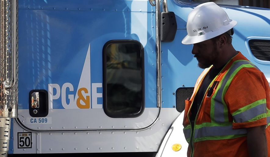 In this Aug. 15, 2019, file photo, a Pacific Gas & Electric worker walks in front of a truck in San Francisco. Pacific Gas & Electric and a group of insurers say they have reached an $11 billion settlement to cover most of the claims from the 2017 and 2018 wildfires in California. The utility said in a statement Friday, Sept. 13, that the tentative agreement covers 85% of the insurance claims, including a fire that decimated the town of Paradise. (AP Photo/Jeff Chiu, File)