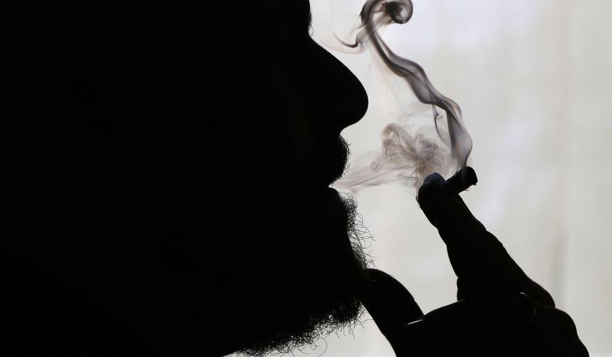 In this Nov. 21, 2014 file photo, a man smokes medical marijuana at his home in Belfast, Maine. (AP Photo/Robert F. Bukaty, File)