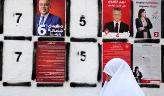 FILE - In this Sept. 4, 2019 file photo, a woman walks past a wall of campaign posters in Tunis. Twenty-six candidates are running for president of Tunisia in a cacophonous election seen as key to securing the country's young democracy. The first-round presidential vote is being held Sunday Sept. 15, 2019. (AP Photo/Hassene Dridi, File)