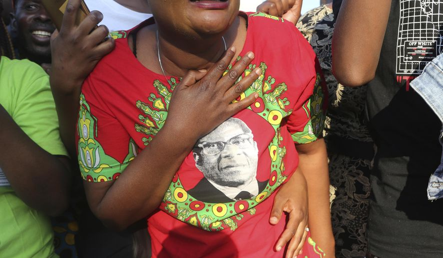 Supporters of Zimbabwe's former ruler Robert Mugabe react upon the arrival of his remains at RG Mugabe airport in Harare, Sept, 11, 2019. As controversy continues around the burial of Mugabe, the capital, Harare, bustles with people coping with the challenges of daily life amid widespread shortages. (AP Photo/Tsvangirayi Mukwazhi, File)