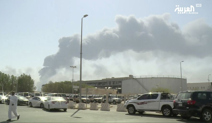 In this image made from a video broadcast on the Saudi-owned Al-Arabiya satellite news channel on Saturday, Sept. 14, 2019, a man walks through a parking lot as the smoke from a fire at the Abqaiq oil processing facility can be seen behind him in Buqyaq, Saudi Arabia. Drones launched by Yemen's Houthi rebels attacked the world's largest oil processing facility in Saudi Arabia and another major oilfield Saturday, sparking huge fires at a vulnerable chokepoint for global energy supplies. (Al-Arabiya via AP) TV OUT NO SALES