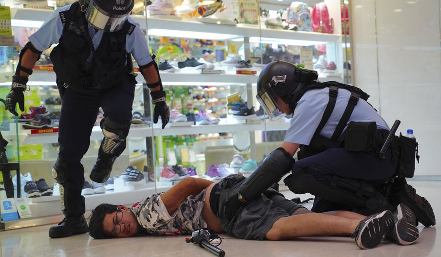 Police detain a young man after fights broke out between pro-China supporters and anti-government protesters at Amoy Plaza in the Kowloon Bay district in Hong Kong, Saturday, Sept. 14, 2019. The clashes came after several nights of peaceful rallies that featured mass singing at shopping malls by supporters of the months-long protests demanding democratic reforms. (AP Photo/Vincent Yu)
