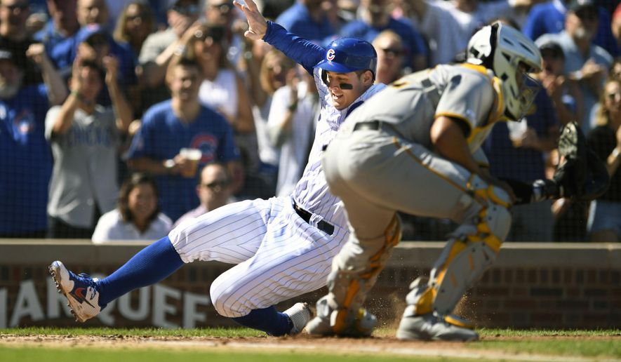 Chicago Cubs' Anthony Rizzo slides safely into home plate on a Nicholas Castellanos double as Pittsburgh Pirates catcher Elias Diaz waits for the throw during the second inning of a baseball game Saturday, Sept. 14, 2019, in Chicago. (AP Photo/Paul Beaty)