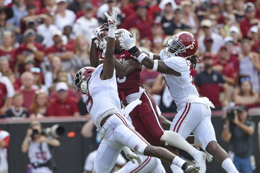 South Carolina's Shi Smith, center, catches a touchdown pass while defended by Alabama's Jordan Battle, left, and Shyheim Carter during the first half of an NCAA college football game Saturday, Sept. 14, 2019, in Columbia, S.C. (AP Photo/Richard Shiro)