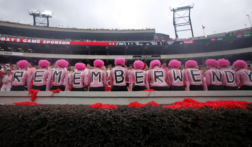 """Georgia fans observe a moment of silence in horror of Wendy Anderson, wife of Arkansas State head coach Blake Anderson before an NCAA college football game Saturday, Sept. 14, 2019, in Athens, Ga. Fans were encouraged to """"pink out"""" the stadium for Wendy Anderson who died from breast cancer in August. (AP Photo/John Bazemore)"""