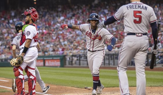 Atlanta Braves Ronald Acuna Jr., center, is congratulated by teammate Freddie Freeman, right,  after scoring a run during the seventh inning of a baseball game against the Washington Nationals in Washington, Saturday, Sept. 14, 2019. (AP Photo/Manuel Balce Ceneta) ** FILE **