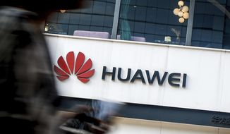FILE - In this July 30, 2019, file photo a woman walks by a Huawei retail store in Beijing. The U.S. government gave chipmakers and technology companies a 90-day extension to sell products to technology giant Huawei. China has criticized Washington's opposition to Chinese-made next-generation telecoms technology after Vice President Mike Pence called on Iceland and other governments to find alternatives. (AP Photo/Andy Wong, File)