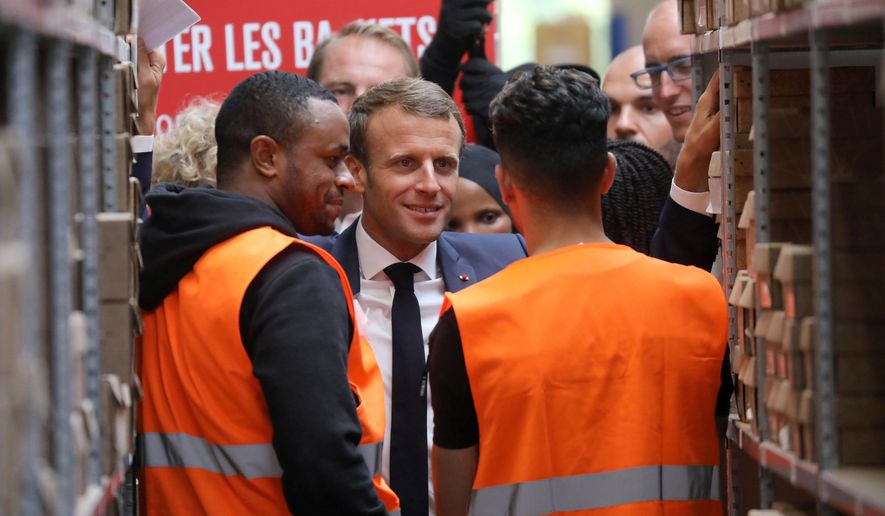 In this photo taken on Tuesday Sept. 10, 2019 French President Emmanuel Macron listens to warehouse workers in Bonneuil-sur-Marne, southwest of Paris. French President Emmanuel Macron was a world away from the glamor of hosting world leaders at a G-7 summit a few weeks earlier. This time, those he was trying to win over weren't President Donald Trump and other heads of states in the luxurious seaside resort of Biarritz, but workers struggling to make ends meet. (Ludovic Marin, Pool via AP)
