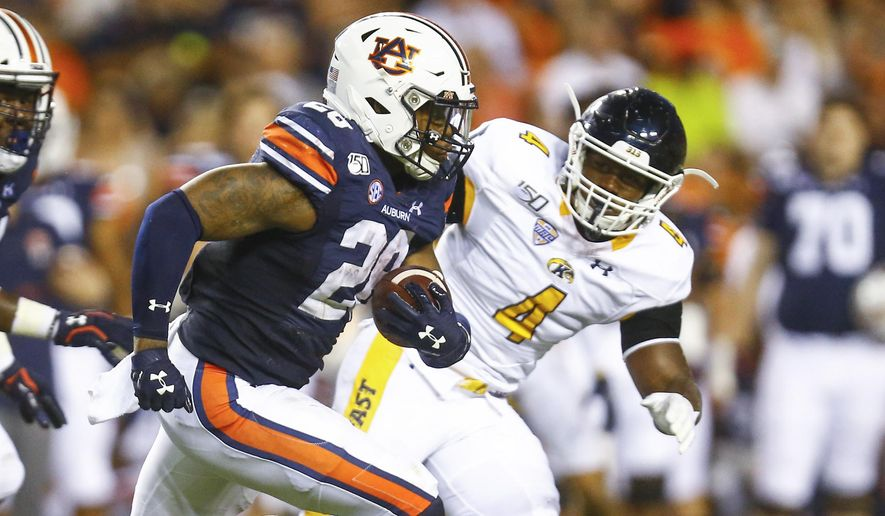 Auburn running back JaTarvious Whitlow (28) carries the ball as he tries to get around Kent State linebacker Cepeda Phillips (4) during the first half of an NCAA college football game Saturday, Sept. 14, 2019, in Auburn, Ala. (AP Photo/Butch Dill)