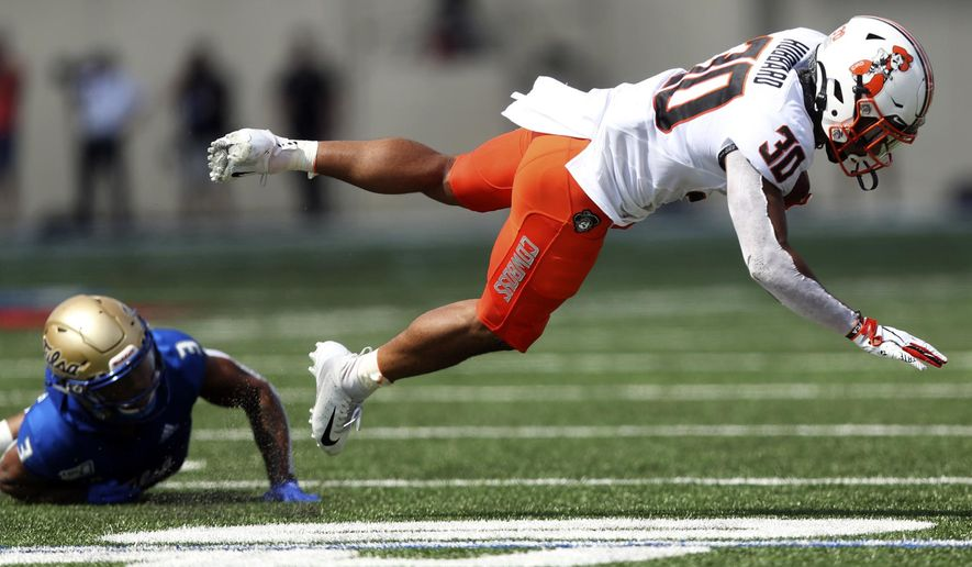 Oklahoma State running back Chuba Hubbard (30) flies through the air after being tackled by Tulsa safety Cristian Williams (3) during an NCAA college football game, Saturday, Sept. 14, 2019, in Tulsa, Okla. (Ian Maule/Tulsa World via AP)