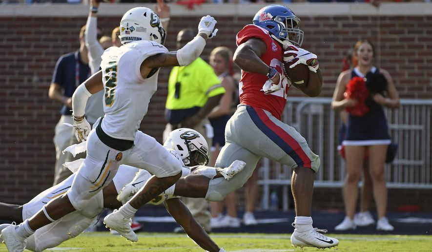 Mississippi running back Scottie Phillips (22) runs past Southeastern Louisiana defensive backs Dejion Lynch (6) and Donniel Ward-Magee (8) for a 27-yard touchdown during the first half of an NCAA college football game in Oxford, Miss., Saturday, Sept. 14, 2019. Mississippi won 40-29. (AP Photo/Thomas Graning)