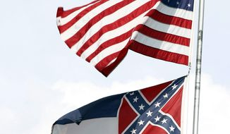 In this Oct. 8, 2015 photograph, the American and Mississippi state flags fly on a flag pole outside the City Hall in McComb, Miss. It's a divisive issue that makes politicians squirm: Should Mississippi remove a Confederate battle emblem from its state flag, or stick with the banner it has flown since Reconstruction?  (AP Photo/Rogelio V. Solis)