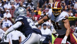 Dallas Cowboys running back Ezekiel Elliott (left) runs the ball against Washington Redskins outside linebacker Ryan Kerrigan (right) during an NFL football game, Sunday, Sept. 15, 2019, in Landover, Md. (AP Photo/Mark Tenally) **FILE**