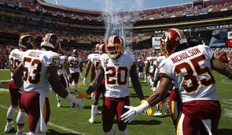 Washington Redskins strong safety Landon Collins (20) is greeter by teammates Washington Redskins inside linebacker Jon Bostic (53) and strong safety Montae Nicholson (35) before the start of the first half of an NFL football game against the Dallas Cowboys, Sunday, Sept. 15, 2019, in Landover, Md. (AP Photo/Alex Brandon)