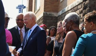 """Former Vice President and presidential candidate Joe Biden, center, left, speaks with an attendee as he joins Sen. Doug Jones and Birmingham Mayor Randall Woodfin at a wreath laying after a service at 16th Street Baptist Church in Birmingham, Ala., Sunday, Sept. 15, 2019. Visiting the black church bombed by the Ku Klux Klan in the civil rights era, Democratic presidential candidate Biden said Sunday the country hasn't """"relegated racism and white supremacy to the pages of history"""" as he framed current tensions in the context of the movement's historic struggle for equality. (Ivana Hrynkiw/The Birmingham News via AP)"""