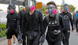 Protesters carry bricks during a demonstration near Central Government Complex in Hong Kong, Sunday, Sept. 15, 2019 as violence flared anew after thousands of pro-democracy supporters marched through downtown in defiance of a police ban. (AP Photo/Kin Cheung)