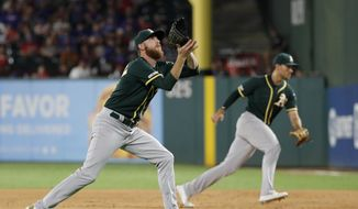 Oakland Athletics relief pitcher Paul Blackburn, left, reaches to field a groundout by Texas Rangers' Rougned Odor as first baseman Matt Olson, rear, moves to cover first in the fourth inning of a baseball game in Arlington, Texas, Saturday, Sept. 14, 2019. (AP Photo/Tony Gutierrez)