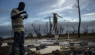 Jeffrey Roberts, 49, eats a plate of food while searching through the rubble of his relatives' home which was destroyed by Hurricane Dorian in Pelican Point, Grand Bahama, Bahamas, Saturday, Sept. 14, 2019. The death toll from the hurricane stands at 50 and the number of missing at an alarming 1,300 people, although officials caution the list is preliminary and many people could just be unable to connect with loved ones. (AP Photo/Ramon Espinosa)