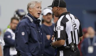 Seattle Seahawks head coach Pete Carroll, left, talks with back judge Greg Steed during the second half of an NFL football game against the Cincinnati Bengals, Sunday, Sept. 8, 2019, in Seattle. (AP Photo/John Froschauer)