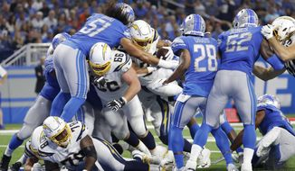 Los Angeles Chargers running back Austin Ekeler (30) fumbles the ball against the Detroit Lions in the second half of an NFL football game in Detroit, Sunday, Sept. 15, 2019. (AP Photo/Rick Osentoski)
