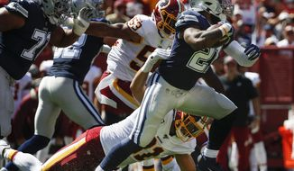 Dallas Cowboys running back Ezekiel Elliott (21) breaks away from Washington Redskins outside linebacker Ryan Kerrigan (91) in the first half of an NFL football game, Sunday, Sept. 15, 2019, in Landover, Md. (AP Photo/Alex Brandon)