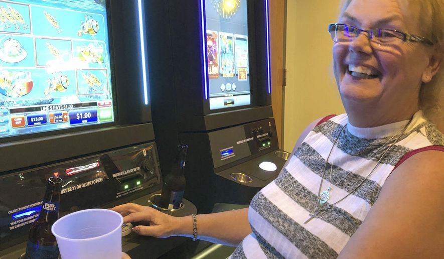 Carol Johnson plays an electronic pull tab machine in Mandan, North Dakota, Thursday, Sept. 5, 2019. In the year since the state launched electronic pull tabs, charities and the state's treasury have ballooned with cash from the game that instantly became the state's most popular form of gambling. But critics say the e-pull tabs, a modern version of tear-off paper pull tabs, are simply slot machines in disguise that take away profits from the state's American Indian casinos and have caused problem gambling to soar. (AP Photo/James MacPherson).