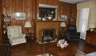 The Living room and fireplace mantle is a location in Mattie Coldiron's historic home where many wedding photographs have been taken. (Kevin Goldy/The Daily Independent via AP)