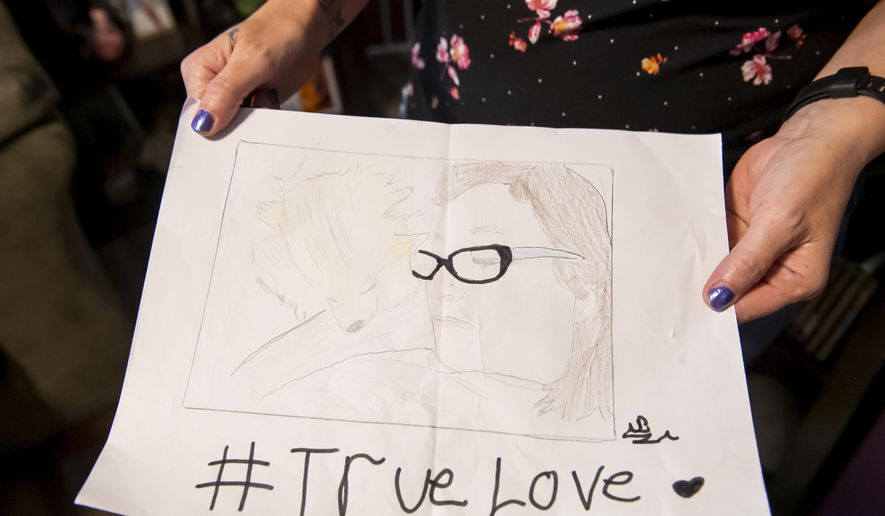 """In this July 25, 2019 photo, Ashton Brooks stepmother, Karen Brooks, holds a drawing that Ashton gave her for Mother's Day this year., at their home in Hanover, Pa. Ashton enjoys drawing, especially characters from his favorite manga, """"My Hero Academia."""" Ashton came out as transgender in early 2019. (Dan Rainville/The Evening Sun via AP)"""