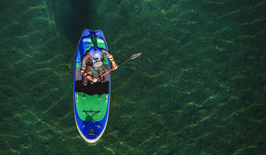 In a Sept. 5, 2019 photo,Jimmy Reed of Whitefish paddle boards on the Middle Fork of the Flathead River below Belton Bridge in West Glacier, Mont. (Hunter D'Antuono/Flathead Beacon via AP)