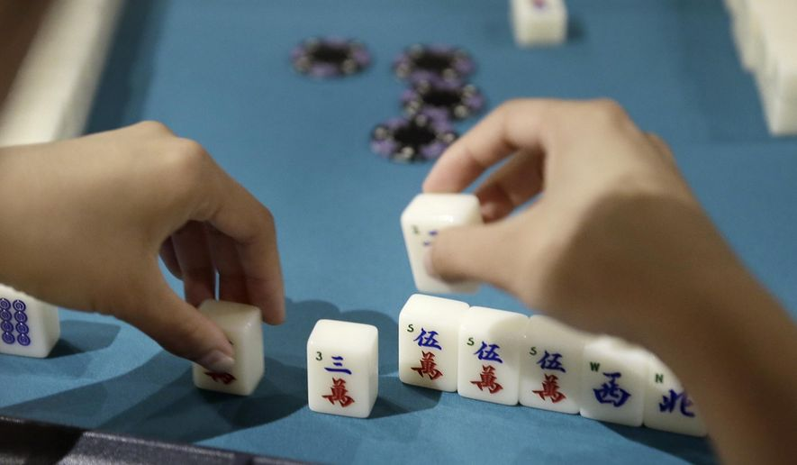 In this July 17, 2018 photo, Inquirer writer Bethany Ao makes a move while playing Mahjong, with The Philly Mah-Jawng Club, at ThirstyDice in the Spring Garden section of Philadelphia. (Elizabeth Robertson/The Philadelphia Inquirer via AP)