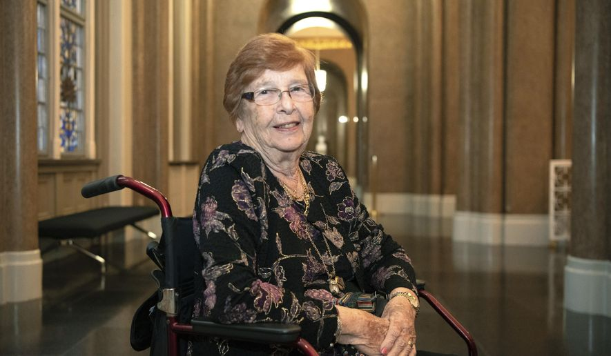 In this Wednesday Sept. 11, 2019 photo, Holocaust survivor Helga Melmed poses for a portrait during an event celebrating the 50th anniversary of a program for people expelled and persecuted by the Nazis and bringing tens of thousands of them back to their home city for one-week trips in Berlin. Helga Melmed was 14 years old when the Nazis forced her family on a train and deported her from her hometown of Berlin to the Jewish ghetto in Lodz in 1941 and she finally freed by British soldiers in 1945 from Bergen-Belsen. (Paul Zinken/dpa via AP)