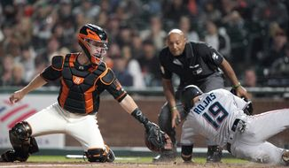 Miami Marlins' Miguel Rojas (19) is safe at home as San Francisco Giants catcher Buster Posey, left, can't make the tag in time during the eighth inning of a baseball game Saturday, Sept. 14, 2019, in San Francisco. (AP Photo/Tony Avelar)
