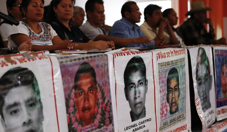 Parents of some of the 43 missing teacher's college students sit behind posters depicting their missing loved ones, during a press conference following a private meeting they had with President Andres Manuel Lopez Obrador, in Mexico City, Wednesday, Sept. 11, 2019. As the fifth anniversary of the students' disappearance at the hands of police approaches, relatives complained Wednesday that progress in the case has been too slow and some institutions are uncooperative. (AP Photo/Rebecca Blackwell)