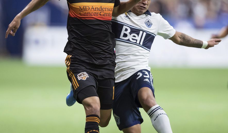 Houston Dynamo's Jose Bizama, left, and Vancouver Whitecaps' Michaell Chirinos vie for the ball during the first half of an MLS soccer game in Vancouver, on Saturday Sept. 14, 2019. (Darryl Dyck/The Canadian Press via AP)