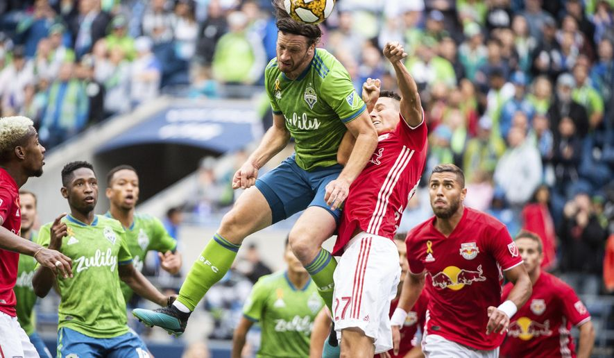 Seattle Sounders defender Gustav Svensson (4) goes up for header against New York Red Bulls midfielder Sean Davis (27) on Sunday, Sept. 15, 2019, in the first half of a MLS soccer match at CenturyLink Field in Seattle, Wash. (Joshua Bessex/The News Tribune via AP)