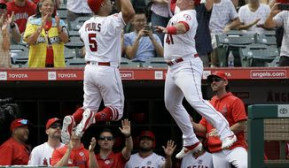 Los Angeles Angels designated hitter Albert Pujols, left, celebrates with Justin Bour, right, after hitting a three-run home run against the Tampa Bay Rays during the fifth inning of a baseball game in Anaheim, Calif., Sunday, Sept. 15, 2019. (AP Photo/Alex Gallardo)