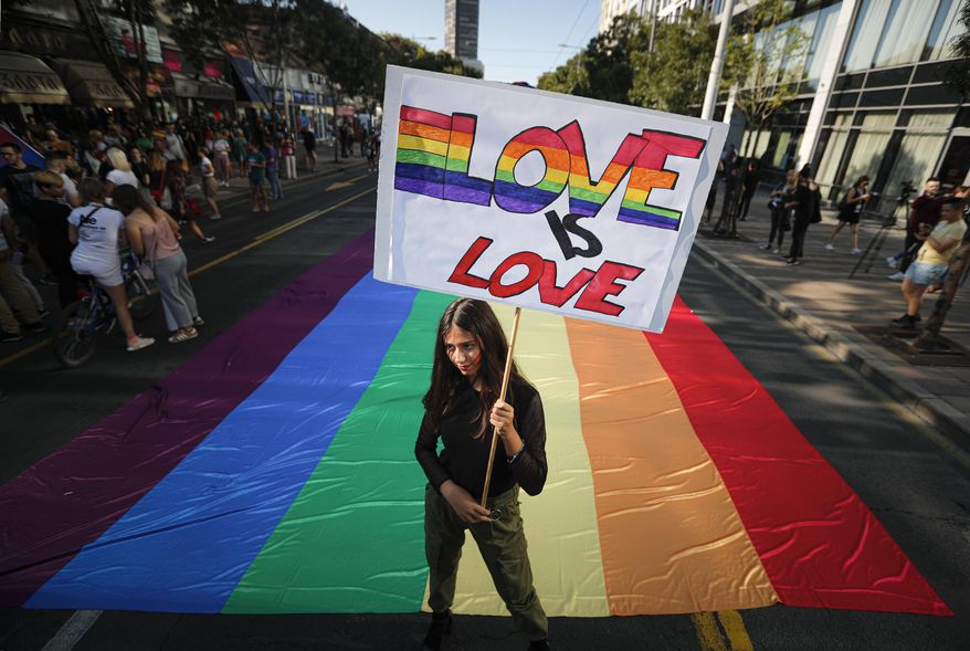 A participant holds a banner during the annual gay pride in Belgrade, Serbia, Sunday, Sept. 15, 2019. (AP Photo/Darko Vojinovic)
