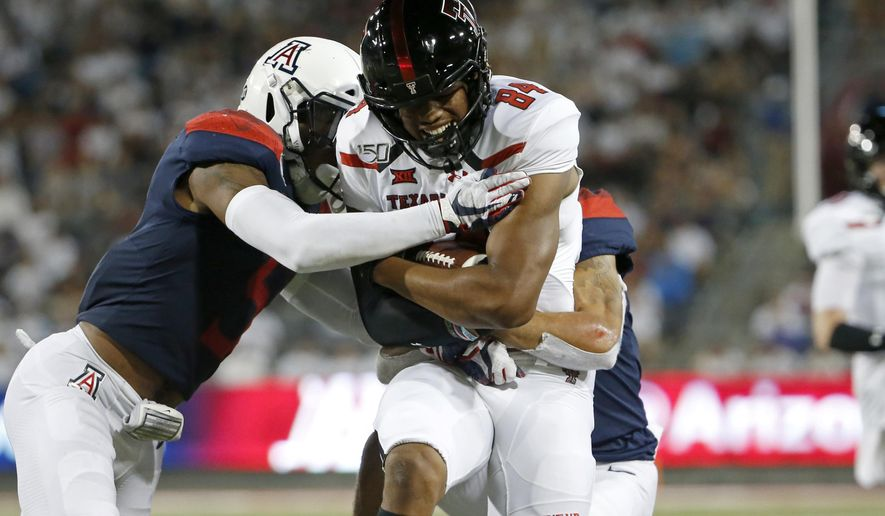 Texas Tech wide receiver Erik Ezukanma (84) is tackled by Arizona safety Christian Young, left, and cornerback Lorenzo Burns, right, after a first down catch and run during the first half of an NCAA college football game, Saturday, Sept. 14, 2019, in Tucson, Ariz. (AP Photo/Ralph Freso)