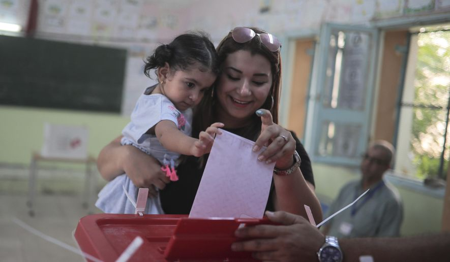 A voter casts her ballot as she carries her daughter inside a polling station during the first round of the presidential election, in Tunis, Tunisia, Sunday Sept. 15, 2019. Tunisians are casting ballots in their North African country's second democratic presidential election, choosing among 26 candidates for a leader who can safeguard its young democracy and tackle its unemployment and corruption. (AP Photo/Mosa'ab Elshamy)