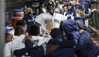 Seattle Mariners' Shed Long is congratulated by teammates in the dugout after hitting a solo home run off Chicago White Sox starting pitcher Dylan Cease during the fifth inning of a baseball game Saturday, Sept. 14, 2019, in Seattle. (AP Photo/Stephen Brashear)