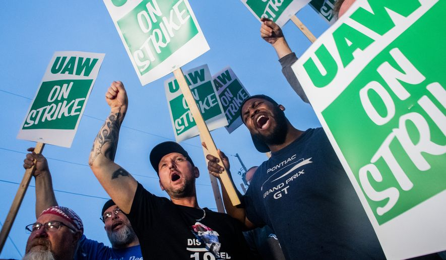 General Motors employees Bobby Caughel, left, and Flint resident James Crump, shout out as they protest with other GM employees, United Auto Workers members and labor supporters outside of the Flint Assembly Plant on Monday, Sept. 16, 2019 in Flint, Mich. Thousands of members of the United Auto Workers walked off General Motors factory floors or set up picket lines early Monday as contract talks with the company deteriorated into a strike. (Jake May/The Flint Journal via AP)