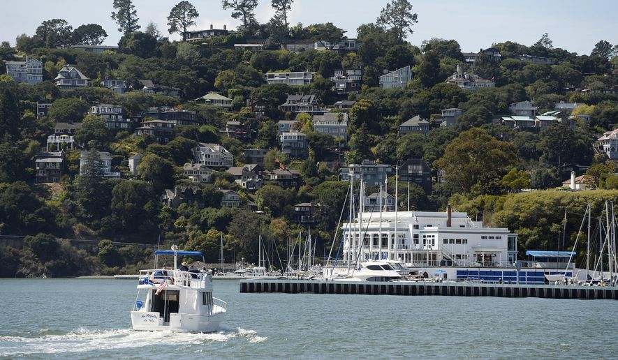 A boat motors toward the Corinthian Yacht Club in Tiburon, Calif., Monday, Sept. 16, 2019, with the town of Belvedere on the hill in the background. A Belvedere father was arrested on manslaughter charges after his 11-year-old son was thrown overboard a boat in the San Francisco Bay and killed after being struck by the vessel, police said. (Alan Dep/Marin Independent Journal via AP)
