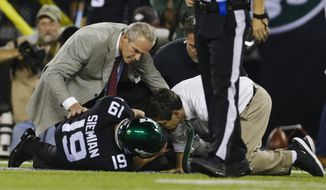 Trainers check on New York Jets quarterback Trevor Siemian (19) after he was injured during the first half of an NFL football game against the Cleveland Browns, Monday, Sept. 16, 2019, in East Rutherford, N.J. (AP Photo/Adam Hunger)