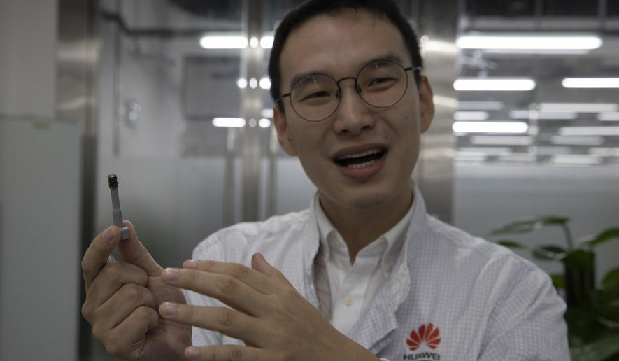 In this Aug. 21, 2019, photo, a Huawei research engineer holds up a coated screw designed to reduce signal interference at the Huawei Materials lab in Dongguan in Southern China's Guangdong province. Facing a ban on access to U.S. technology, Chinese telecom equipment maker Huawei is showing it increasingly can do without American components and compete with Western industry leaders in pioneering research. (AP Photo/Ng Han Guan)