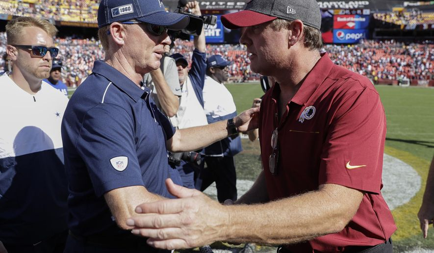 Dallas Cowboys head coach Jason Garrett, left, and Washington Redskins head coach Jay Gruden, right, meeting on the field after the end of an NFL football game, Sunday, Sept. 15, 2019, in Landover, Md. Dallas won 31-21. (AP Photo/Evan Vucci)