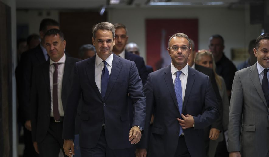 Greece's Prime Minister Kyriakos Mitsotakis center left, and Greek Finance Minister Christos Staikouras, center right, arrive at a meeting in Athens, on Wednesday, Sept. 11, 2019. Mitsotakis chaired Wednesday a meeting of cabinet ministers on economic policy. (AP Photo/Petros Giannakouris)