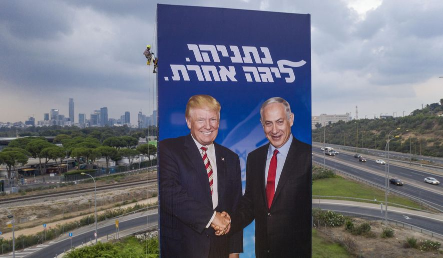 """FILE - In this Sunday, Sept. 8, 2019 file photo, a worker hangs an election campaign billboard of the Likud party showing US President Donald Trump, left, and Israeli Prime Minister Benjamin Netanyahu in Tel Aviv. Israel is heading to an unprecedented repeat election next week with no guarantee that the do-over vote will produce a more decisive result than an inconclusive one last April. Hebrew on the billboard reads """"Netanyahu, another league."""" (AP Photo/Oded Balilty, File)"""