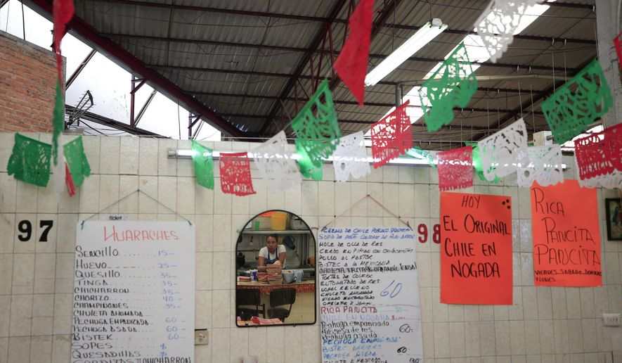 """In this Sept. 10, 2019 photo, a sign advertises in Spanish, """"Today, the traditional chile en nogada,"""" at El Sabor, a family-owned restaurant inside the Juarez Market that for decades has been serving up chiles en nogada in the weeks leading up to Mexico's independence celebrations, in Mexico City. Although the 200 peso ($10.50) price tag at El Sabor is half that at high end restaurants, the traditional ingredients and hours of labor that go into making the sweet and salty dish mean it is still the priciest item on their menu, a seasonal treat for fans of the dish. (AP Photo/Rebecca Blackwell)"""